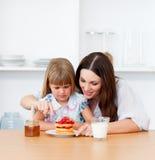 Petite fille affectueuse et sa mère prenant le petit déjeuner Images stock