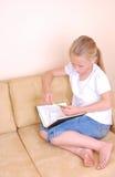 Petite fille affichant une note images stock