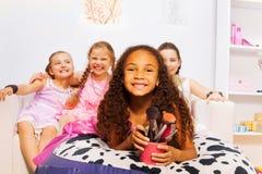 Petite fille africaine et ses amis s'étendant sur le lit Image libre de droits