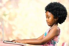 Petite fille africaine mignonne avec la coiffure Afro dactylographiant sur l'ordinateur portable image stock