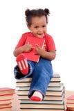 Petite fille africaine s'asseyant sur beaucoup de livres image stock