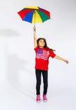 Petite fille afro-américaine de sourire mignonne sautant avec l'umb coloré Image stock