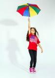 Petite fille afro-américaine de sourire mignonne sautant avec l'umb coloré Photos libres de droits