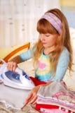 Petite fille aidant avec repasser Photos libres de droits