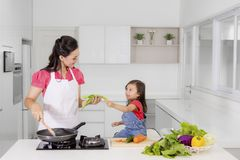 Petite fille aidant sa mère à faire cuire dans la cuisine Photographie stock