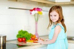 Petite fille aidant sa mère dans une cuisine images libres de droits