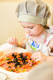 Petite fille ajoutant des ingrédients en pizza Images stock