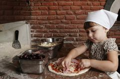 Petite fille ajoutant le lard à la pizza Images stock
