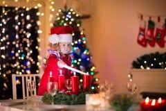 Petite fille allumant des bougies au dîner de Noël Photos stock