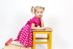 Petite fille 3 années dans une robe rouge avec des arcs dans ses cheveux photo libre de droits