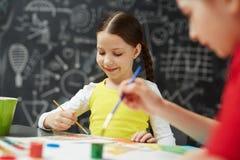 Petite fille appréciant la peinture Image libre de droits