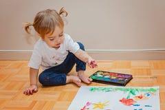 Petite fille apprenant à dessiner avec des aquarelles pendant le temps de sapins Image libre de droits
