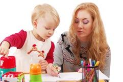 Petite fille apprenant à dessiner avec sa mère Photo stock
