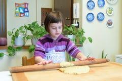 Petite fille apprenant à faire des pâtes avec une goupille Photos libres de droits