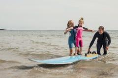 Petite fille apprenant comment surfer Photographie stock