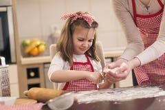 Petite fille arrosant la farine au-dessus de la table de cuisine photographie stock