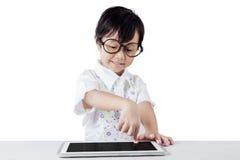 Petite fille asiatique à l'aide du comprimé sur la table photographie stock libre de droits