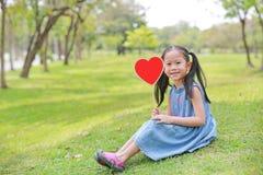 Petite fille asiatique adorable d'enfant tenant le label vide de coeur se reposant sur la pelouse verte photo libre de droits