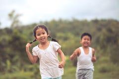 Petite fille asiatique ayant l'amusement à courir et jouer avec son ami Image stock