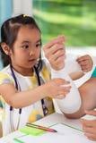 Petite fille asiatique bandant le bras du papa photographie stock