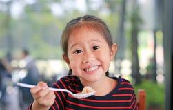 Petite fille asiatique de sourire d'enfant s'asseyant au café et mangeant le petit déjeuner avec regarder directement la caméra photographie stock libre de droits