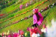 Petite fille asiatique de sourire s'asseyant sur le gisement de fleur Images stock