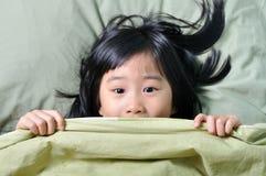Petite fille asiatique effrayée se cachant derrière la couverture Photographie stock libre de droits