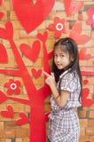 Petite fille asiatique et arbre d'amour rouge de coeur. Photographie stock