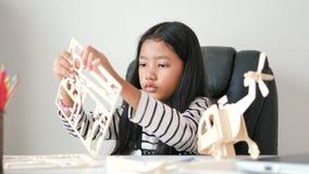 Petite fille asiatique fabriquant un modèle en bois avec le bonheur pour l'auto-apprentissage et le concept d'éducation à la mais clips vidéos