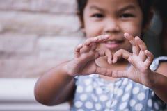 Petite fille asiatique faisant la forme de coeur avec des mains Image stock