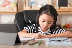 Petite fille asiatique faisant le travail sur le foyer choisi de table en bois SH Photographie stock
