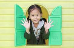Petite fille asiatique heureuse d'enfant jouant avec la maison de théâtre de jouet de fenêtre dans le terrain de jeu photographie stock