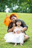 Petite fille asiatique jouant sur l'herbe verte avec sa mère Images libres de droits
