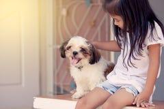 Petite fille asiatique mignonne avec son chien de Shih Tzu Image stock