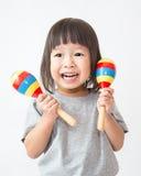 Petite fille asiatique mignonne jouant les maracas images libres de droits