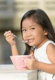 Petite fille asiatique mignonne mangeant des céréales dans le matin Photos stock