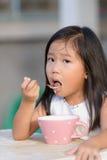 Petite fille asiatique mignonne mangeant des céréales dans le matin Image stock