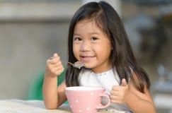 Petite fille asiatique mignonne mangeant des céréales dans le matin photo libre de droits