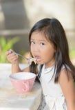Petite fille asiatique mignonne mangeant des céréales dans le matin Images stock