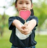 Petite fille asiatique montrant à coeur en bois de signe la profondeur du fie Images libres de droits