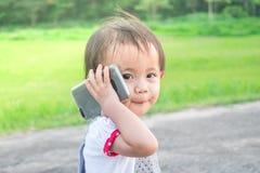 Petite fille asiatique parlant au téléphone intelligent en parc photographie stock