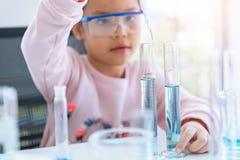Petite fille asiatique tenant et laissant tomber la solution bleue dans le tube à essai dans la chambre de laboratoire au fond de photo stock