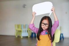 Petite fille asiatique tenant la bulle vide vide de la parole pour dire quelque chose dans la salle de classe avec regarder direc photos libres de droits