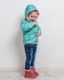 Petite fille attachant sa veste bleue Photo stock