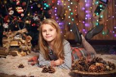 Petite fille attendant un miracle dans des décorations de Noël Photos stock