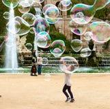 Petite fille attrapant les bulles de savon Photographie stock