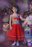 Petite fille aux cheveux foncés dans une robe rouge à côté des fleurs dans un vase image libre de droits