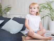 Petite fille aux pieds nus amicale s'asseyant sur un tabouret Images stock
