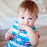 Petite fille aux yeux bleus tenant la main dans la bouche Photo stock