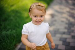 Petite fille aux yeux bruns blonde de sourire marchant sur la rue image stock
